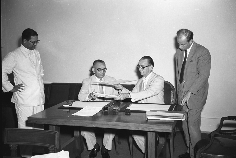 Ph. Studio/June, 1957, A22n/A22a(iv) Photo shows Shri H.M. Patel, Secretary Ministry of Finance (left) and H.E. Mr. Aaro Pakaslahti Head of the Finish Legation in India, who signed the agreement on behalf of their respective Governments, exchanging the Agreement papers, in New Delhi on June 14, 1957.